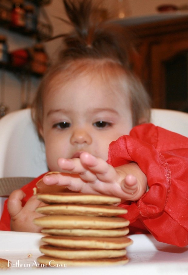 Photo of toddler girl at home reaching for a stack of miniature pancakes.