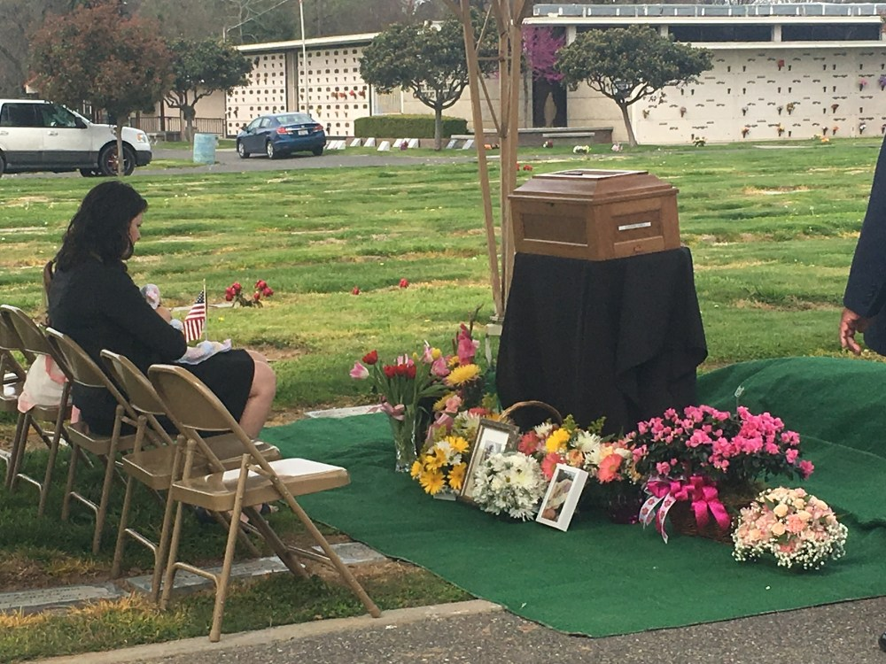 Kathryn Anne Casey at her daughter's funeral, sitting in front of casket at cemetary