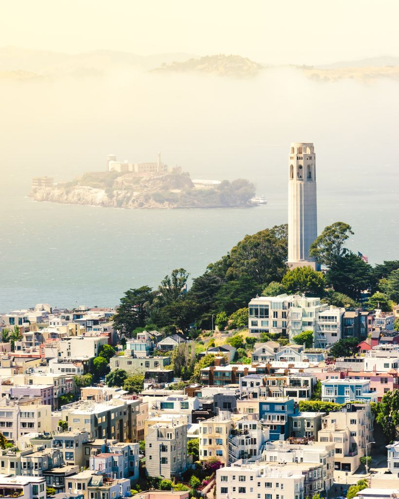 Coit Tower in San Francisco surrounded by buildings, bay water, and fog.