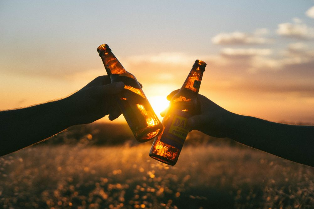 Two people with toasting with beer bottles.
