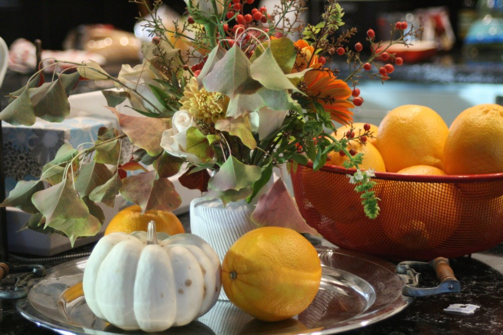 table setting with lemons, pumpkins and fall foliage
