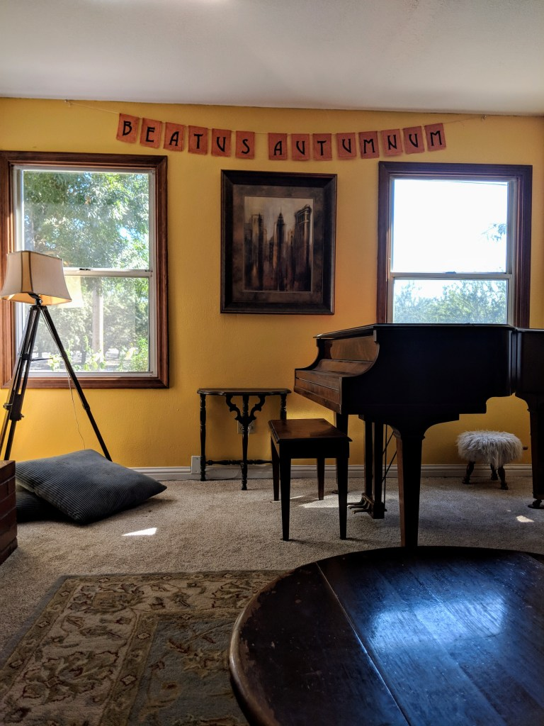 Living room with golden yellow walls and banner reading beautus autumnum, Latin for Blessed Fall