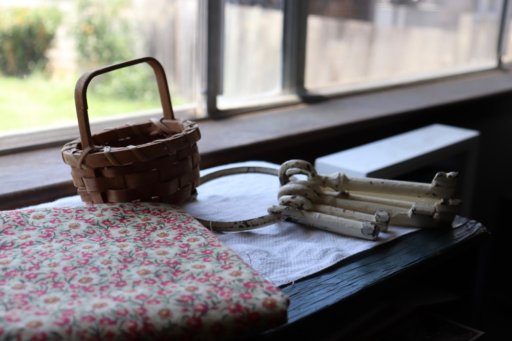 Photograph of home office, cast iron keys, miniature basket and vintage fabric