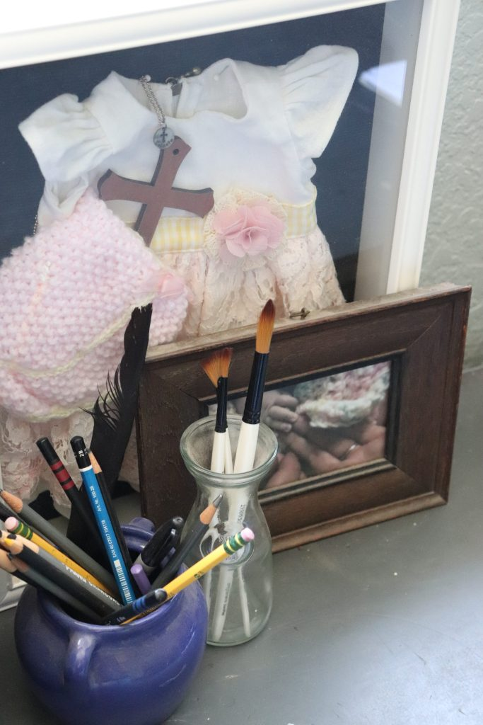 Photograph of home office, pencils, paintbrushes and keepsakes