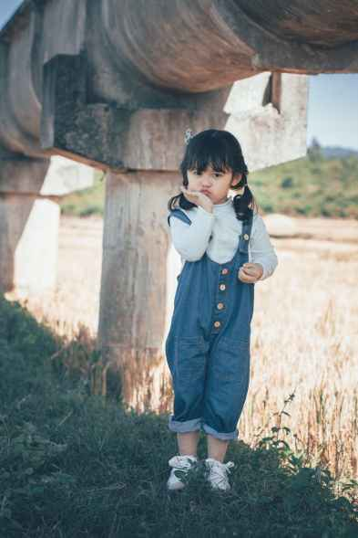 little girl in dungarees