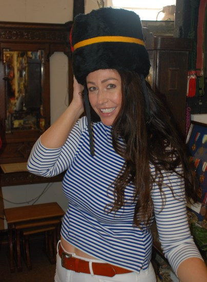Katie trying military hats on at Upstairs Downstairs Antiques Gloucester