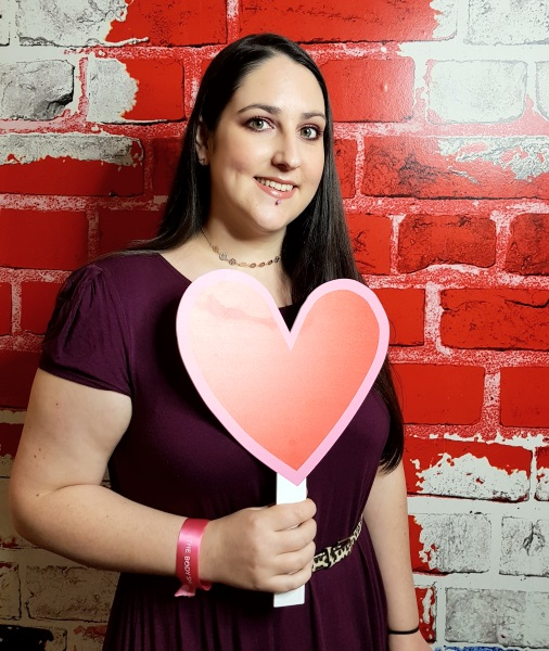 A photo of me holding up a heart prop in front of a red brick wall