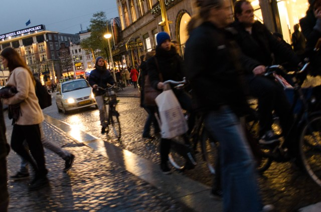 cyclists and pedestrians attempt to navigate the busy street in Dam Square Amsterdam