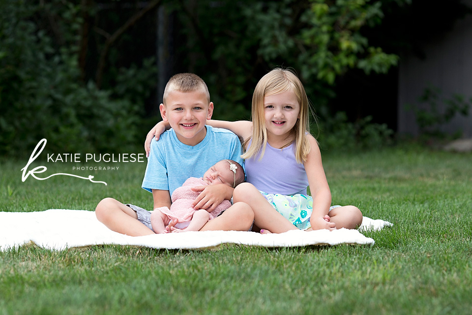 Older siblings posing outside with new baby sister