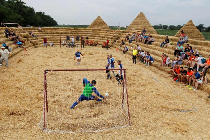 Players attend a football tournament among local amateur teams at a stadium made of straw named Zenit Arena, in the settlement of Krasnoye in Stavropol region