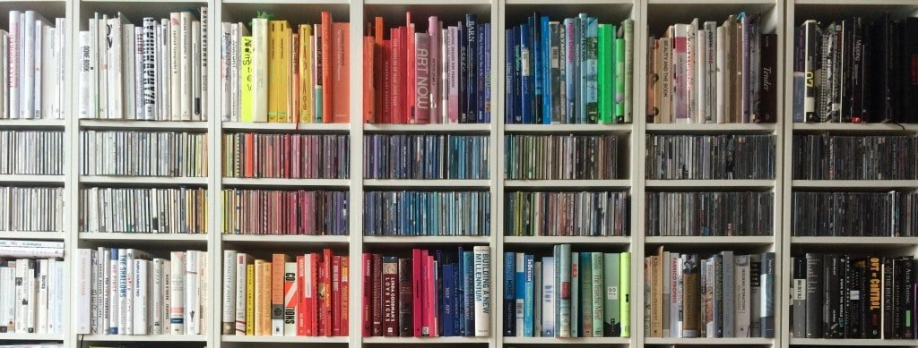A photograph of a white bookshelf filled with books sorted by color.