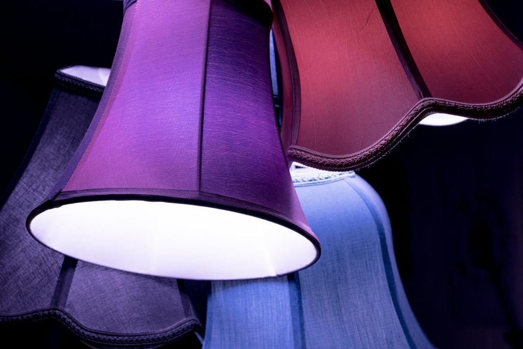 Alt Text: Photograph of four colorful lampshades on a black background, all askew.