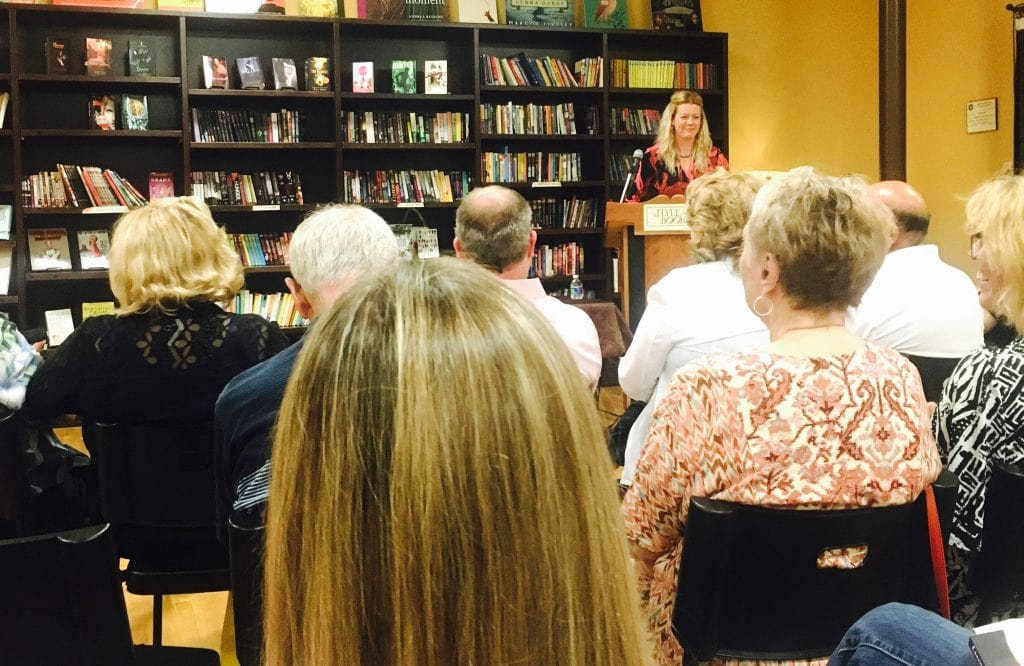 Alt Text: Photograph of the author Katie Rose Guest Pryal reading to a crowd at Flyleaf Books for the launch party for CHASING CHAOS. She stands behind a podium at the front of a room full of people.