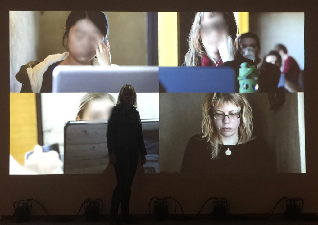 Alt text: A woman in shadow is standing in front of a video projection of four women's faces. Three faces are blurred. The standing woman's own face is not blurred.