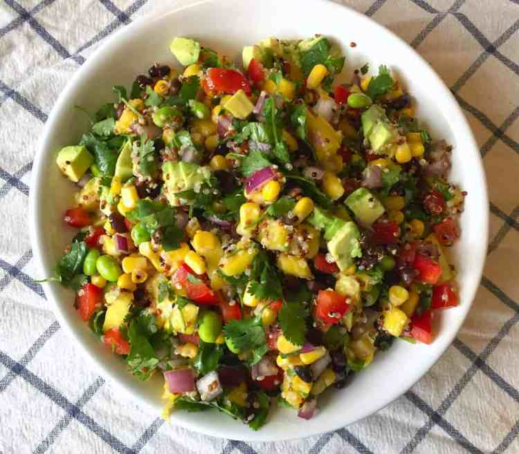A fresh and colorful bean and Corn Salad with mango, avocado, cilantro, and red peppers, in a white bowl.