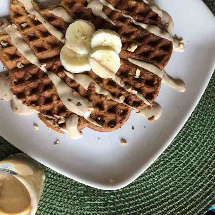 green placemat with white square plate and oat waffle, with banana slices and drizzled peanut butter, shot from above