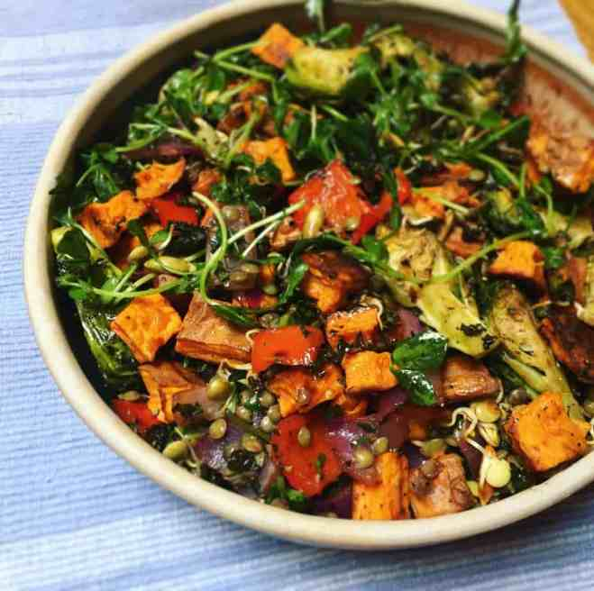 bowl of colorful salad including wilted pea shoots and greens, roasted cubed sweet potatoes, red peppers, lentils, quartered brussels sprouts, with a blue placemat