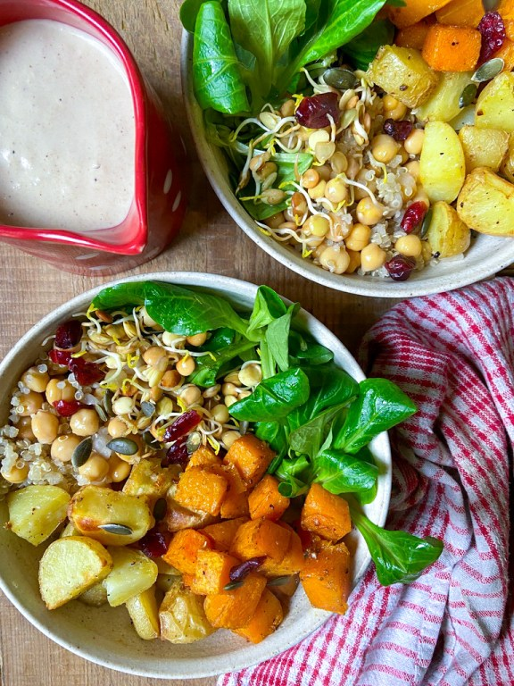 two white bowls next to a towel filled with roasted potatoes and butternut squash, green fresh watercress, and sprouted lentils on top