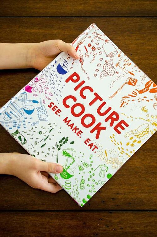 A child's hands grasping a book, titled PICTURE COOK