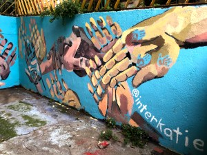 """mural of many hands painted on blue wall. white text reads: """"@interkatie"""""""