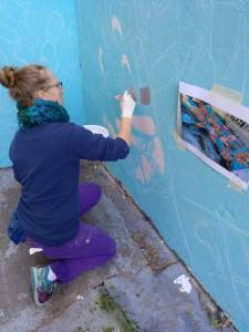a woman kneeling and holding a paintbrush up to a blue wall.