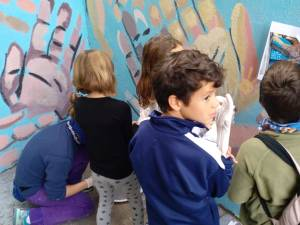 Several 4 to 6 year old children gathered around a blue wall. one wears a latex glove