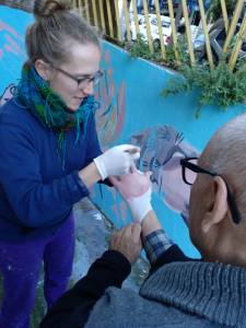 A woman wearing white latex gloves brushing pink paint onto the gloved hand of an older gentleman