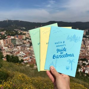 A hand holding three small colorful booklets against a backdrop of mountains and blue sky
