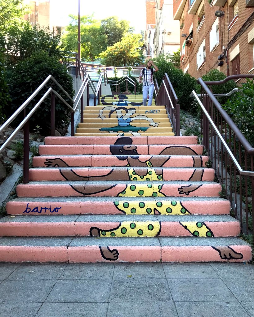 An outdoor staircase with a mural painted on the risers of the steps of a man in a polka-dot leotard