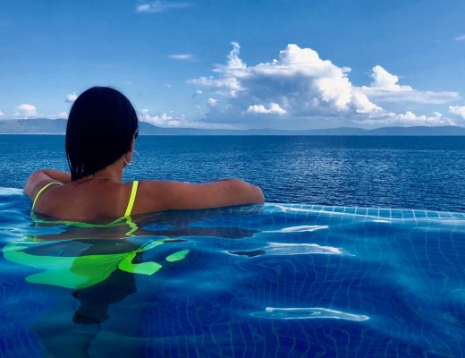 Me from the back in an infinity pool looking out to the sea in Croatia. I have my hair down and a neon green bikini on.