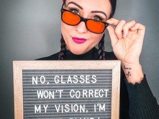 """I am standing holding a board that reads """"No glasses won't correct my vision, I'm going blind!"""" I have my hair in plaits and a black jumper on."""