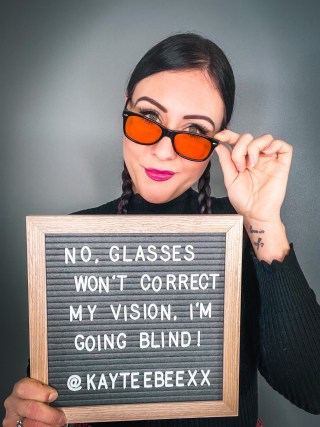 "I am standing holding a board that reads ""No glasses won't correct my vision, I'm going blind!"" I have my hair in plaits and a black jumper on."