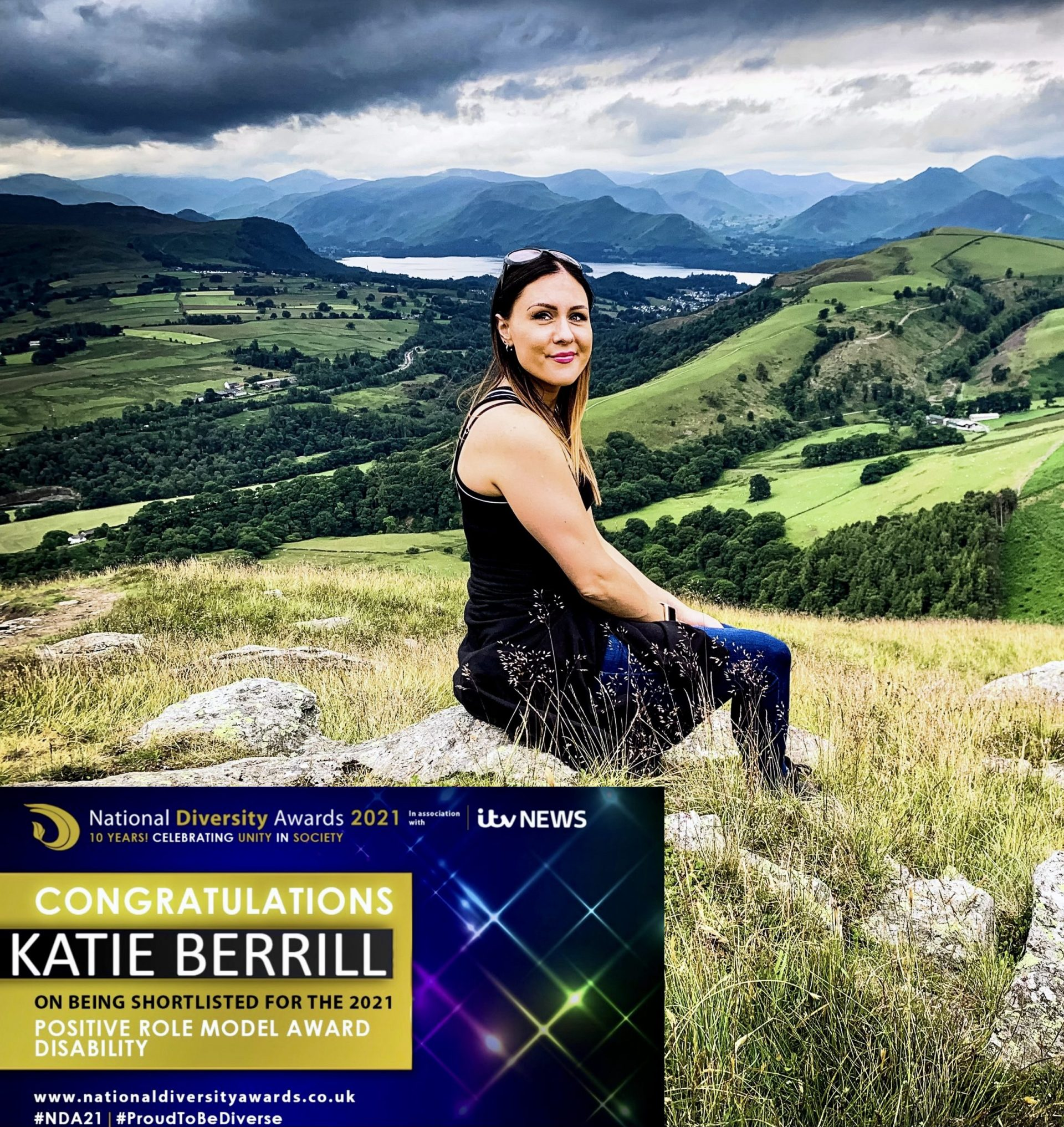 I, a white woman, am sat on a rock looking back towards the camera and it's the Cumbrian hills around me. I have my ombre hair down and am smiling at the camera. The weather is overcast but warm end I am in Summer clothes. There is an image in the bottom of the picture that shows my diversity shortlisted banner