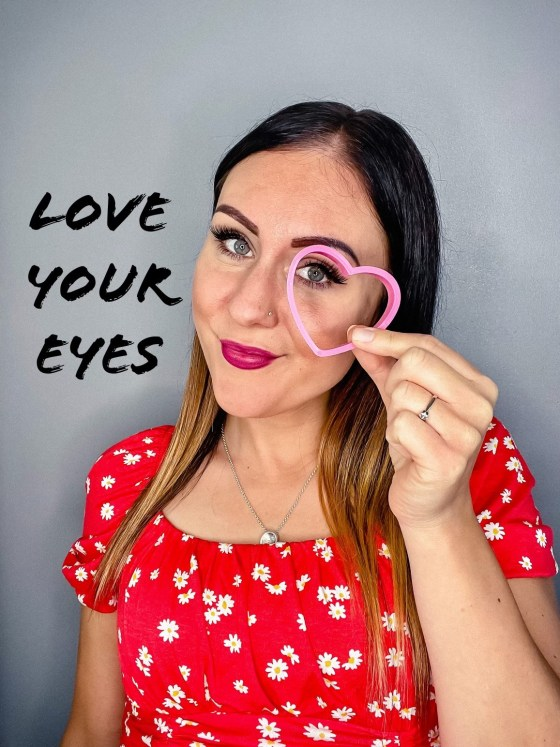"""Picture description - I, a white woman, am standing in front of a grey background I have a red top on and my light hair down and make up on. I am smiling at the camera and holding a pink heart up to my eye. Caption next to me reads """"love your eyes."""""""