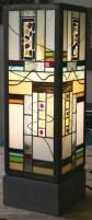 """Lampe contemporaine """"Oslo"""" en vitrail Tiffany constituée de verres plats opalescents de couleurs multiples et de pièces de verres cuites selon la technique du """"Fusing"""". Dessins """"naïfs"""" peints à la grisaille et cuits à 650 °. Socle en béton ciré gris anthracite lui assurant un aspect très moderne et une grande stabilité. 2 tubes fluorescents de 8W fournis assurant un éclairage doux et lumineux."""