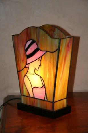 """Lampe """"L'Elegante"""" en vitrail Tiffany. Verre opalescent de couleur rose/blanc et chair pour le personnage et vert, bleu, rose et jaune doré pour le fond. Visage peint à la grisaille et cuit à 600°. Largeur bas 16 cm Largeur haut 21 cm"""