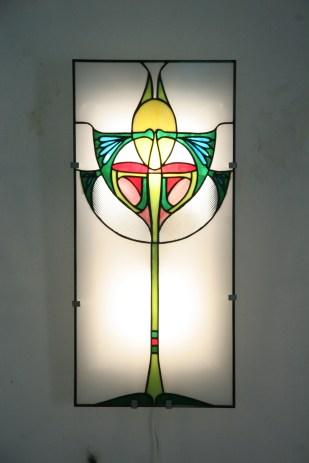 Applique murale vitrail Tiffany, verres opalescents blanc, vert, rose, jaune, bleu et rouge. Montée sur structure électrifiée en acier blanc. Assure un éclairage doux, diffus mais lumineux. Largeur 26 cm Hauteur 56 cm