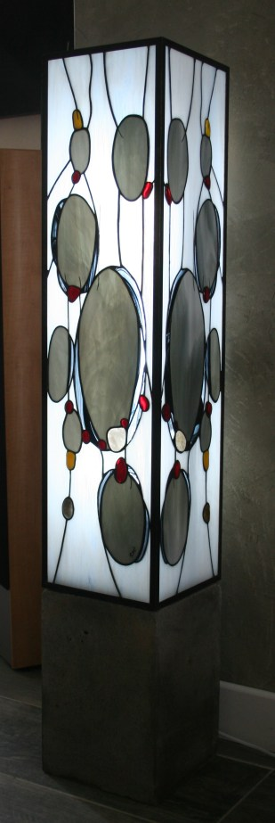 """EXCEPTIONNELLE !! Par sa taille (110 cm de haut, côtés 20*20) et son design : Stonefalls est une représentation graphique d'une chute de pierres, elle est constituée de verres gris et blancs opalescents ainsi que de touches de verre noir. De petits cailloux sont symbolisés en rouge et jaune (fusing : pièces de verres cuits à 750°) mais aussi de véritables galets qui ont été sciés à l'eau pour être translucides. Peinture à la grisaille (cuisson 600 °). Très contemporaine, son socle est en béton pour un rendu """"industriel"""". L'éclairage est assuré par un tube fluorescent pour une belle luminosité et une consommation de seulement 20W"""
