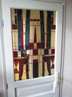 Panneau de vitrail inséré dans une porte qui était pleine et a été évidée. Toujours pour laisser passer la lumière mais occulter la vue. Montage au plomb d'un dessin moderne parsemé de motifs naïfs peints à la grisaille