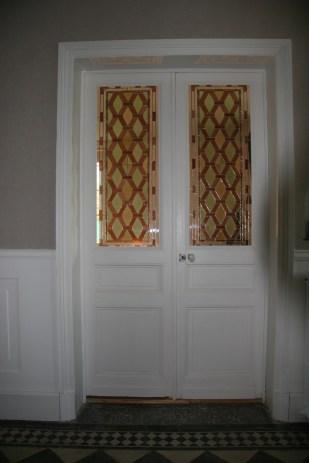 Panneaux de vitraux insérés dans une porte. Une porte pleine a été évidée pour laisser passer la lumière mais occulter la vue