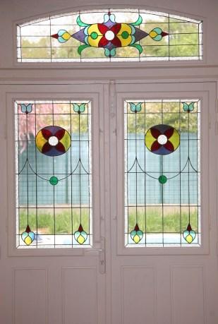 Panneaux de vitraux insérés dans un panneau monté en survitrage, dans une porte d'entrée. Une porte pleine a été évidée pour laisser passer la lumière. Vitrail reprenant les codes de l'Art Nouveau