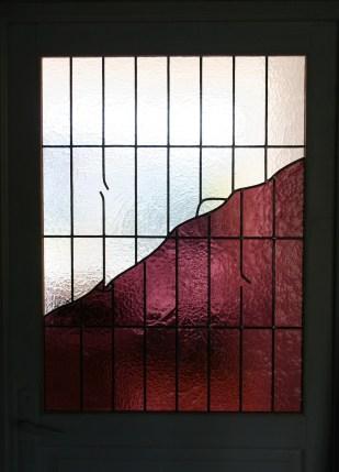 Vitrail au plomb inséré dans une porte dont la partie bois a été enlevée. Dessin simulant un vitrail brisé