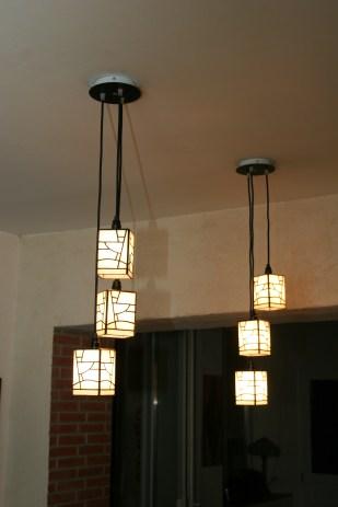 """Ces 2 suspensions sont en vitrail Tiffany au style Art Déco par les coupelles mais au look résolument moderne par leur forme et leur conception. 2 x 3 coupelles suspendues de manière décalées à une structure acier blanche et noire mate conçues pour être fixées directement au plafond. Idéales dans une cuisine moderne par exemple, au dessus du plan de travail pour un éclairage indirecte à la fois doux mais très lumineux. Coupelles constituées de 288 pièces de verres de structure """"torturée"""" et irrégulière d'un blanc mat et d'aspect poudré. Soudures noircies patinées à l'ancienne. Les 6 cordons de suspension sont en textile noir. Dimensions de coupelles : L9 * L9 * H12 cm."""