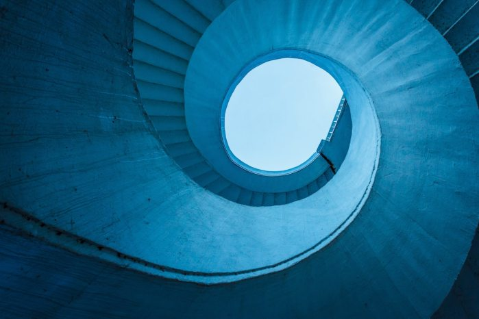Photograph of a blue spiral staircase from below