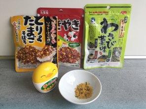 Verschiedene Sorten von Furikake mit Ei, Fleisch und Wasabistückchen.