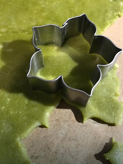 Der ausgerollte Matcha-Teig wird mit zarten Blütenförmchen ausgestochen.