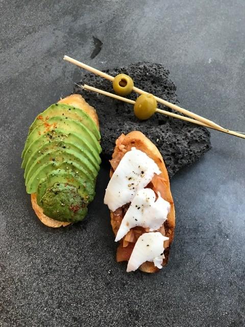 Frische Crustini mit Avocadoscheiben, Tomatenwürfeln und dünnen Scheiben aus Ziegenkäse.