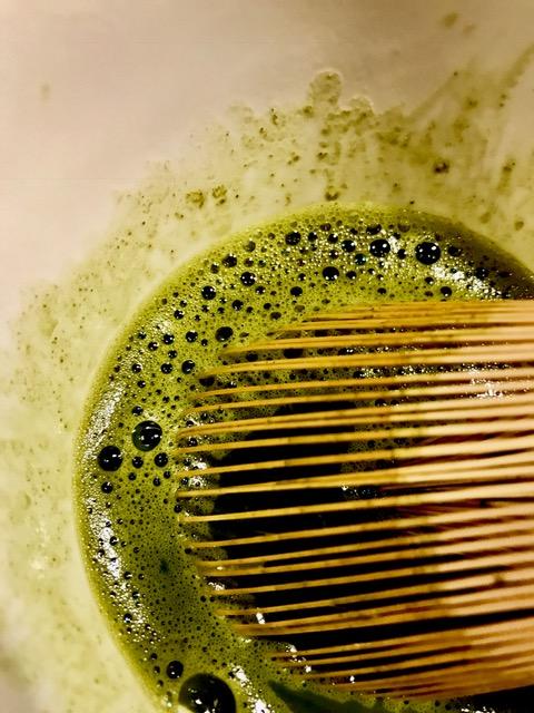 Das grüne Matchapulver wird mit einem japanischen Bambusbesen für das Tiramisu schaumig aufgeschlagen.