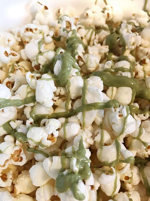 Die geschmolzene weiße Schokolade wird mit Matchapulver vermischt und in einer Schüssel über das Popcorn verteilt. Gut mischen - fertig!