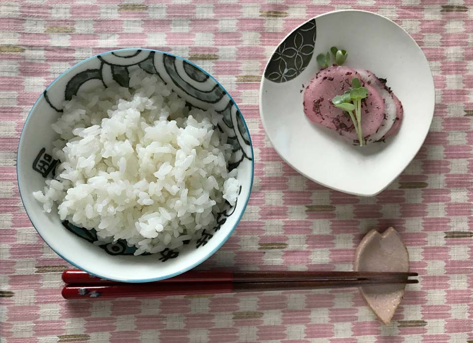 Der eingelegte Rettich wird zusammen mit einer Schale Reis serviert.